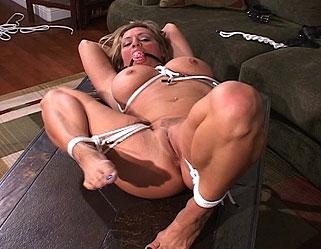 Blonde a gros seins se tortille ligotée sur le canapé montrant ses orifices